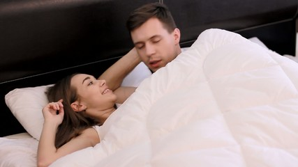 Guy and a girl are watching TV in a bed