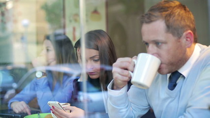 Businesspeople sitting in cafe and use cellphone, streadycam sho