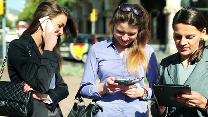 Businesswomen stand on street and use cellphone and tablet, stea