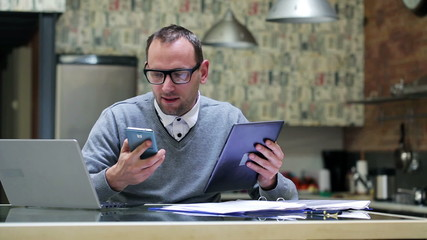 Businessman compare results on cellphone tablet and laptop