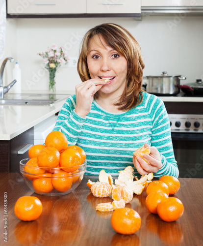 Positive  girl eating mandarin in home