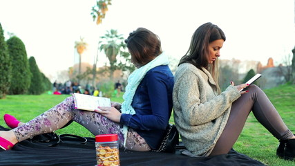 Women sitting in park reading book and using tablet