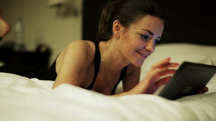 Woman touching screen on tablet and lying in bed, steadycam shot