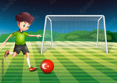 A boy kicking the ball at the field with the flag of Turkey