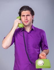 Handsome man with telephone on gray background.