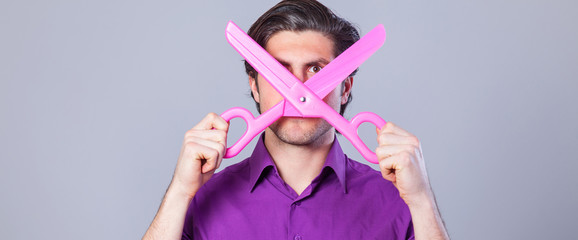Man with huge scissors on gray background.