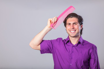 Man with huge comb on gray background.