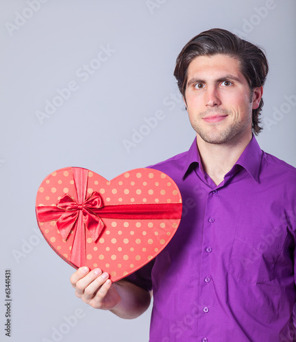 Handsome man with gift on gray background.