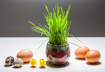 Easter still life with eggs, chickens, grass in a vase.