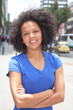 Attractive woman with curly hair and crossed arms in the city