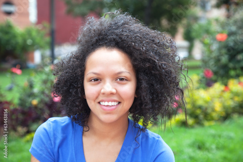Happy young woman with curly hair in a park
