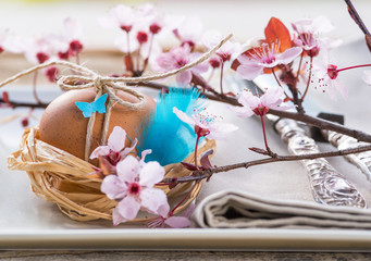 Easter eggs in nest and spring flowers, easter table.