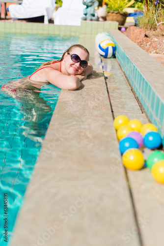 Beautiful young woman smiling in a swimming pool