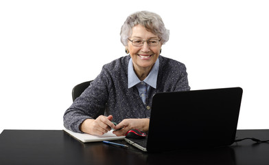 Grey haired old business lady laughing during skype conversation