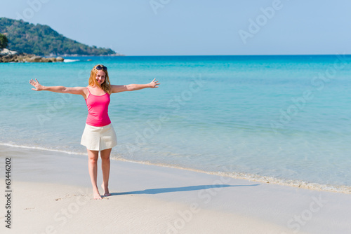 Young woman in pink top and beige skirt walking on beach