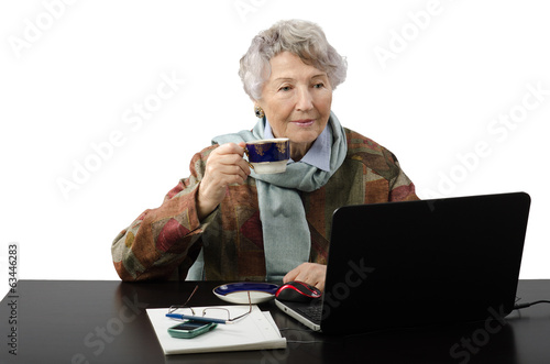 Smiling old lady drinking coffee while reading news on her lepto