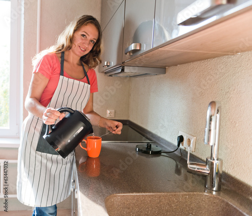 woman pouring hot drink to the mug