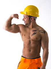 Muscular young construction worker shirtless looking at bicep