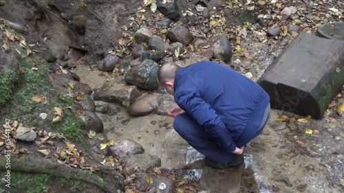 man scoop handful of fresh water from the source between stones