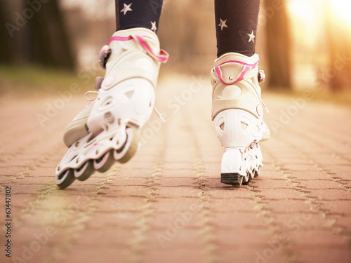 Close up of little girl roller skating in the park