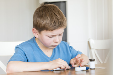 Young boy measuring blood sugar