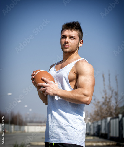 Muscular american football with ball in hand.
