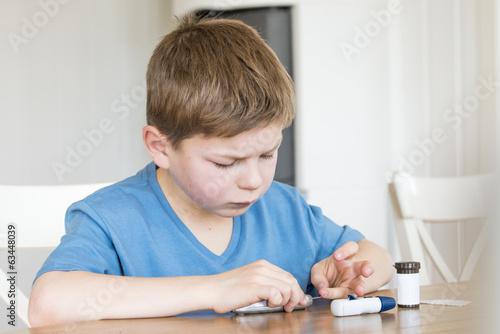 Young boy measuring blood sugar - 63448039