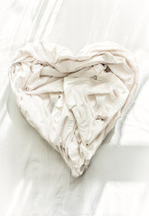 Closeup photo of bed sheet in shape of heart