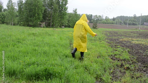 Girl with waterproof raincaot coat walk meadow grass in rain