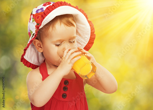 baby girl drinking orange juice in the summer