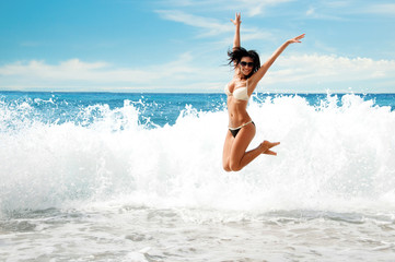 Beautiful young  girl  jumping on sea