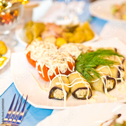 Stuffed tomatoes and eggplant rolls on the table