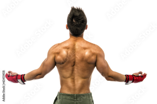 Back of young bodybuilder wearing MMA gloves, with arms open