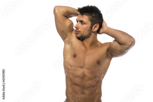 Muscular young bodybuilder showing biceps and ripped abs
