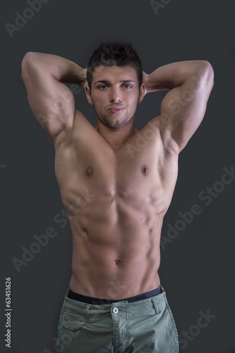canvas print picture Muscular young bodybuilder showing biceps and ripped abs