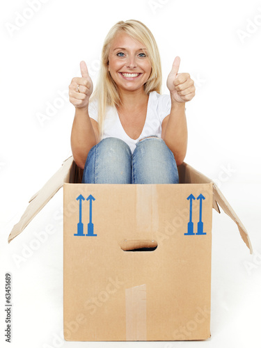Pretty young woman rests in her moving box