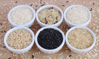 Six varieties of uncooked rice in white bowls on wooden board