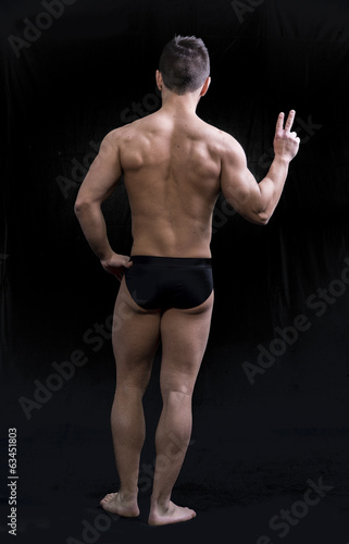 Full body shot of muscular young man seen from the back