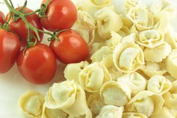 Tortellini crudi con un grappolo di pomodori rossi