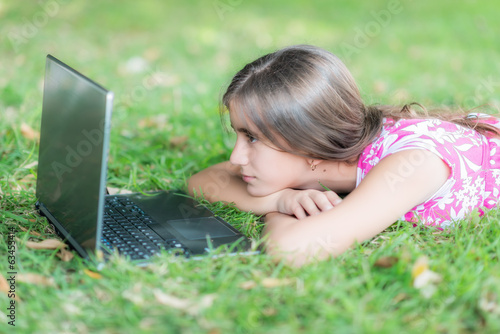 Teenage girl laying in the grass and using her laptop
