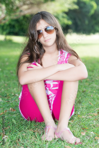 Teenage girl sitting in the grass wearing sunglassses