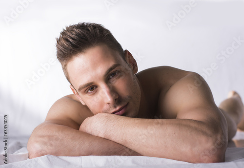 Cute expression, naked young man on white sheets