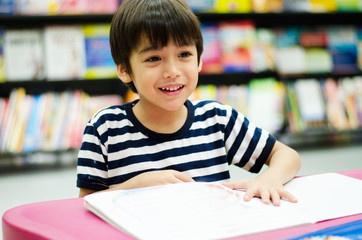 Little Boy in library reading book