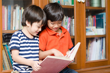Little sibling Boy in library holding book
