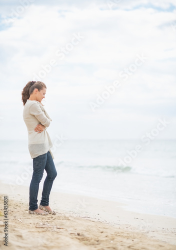 Thoughtful young woman standing on cold beach