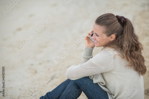 Happy young woman sitting on cold beach and talking mobile phone