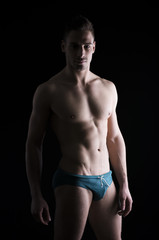 Chiaroscuro photo of shirtless young man standing