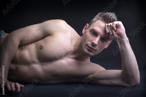 Handsome young man naked on floor.