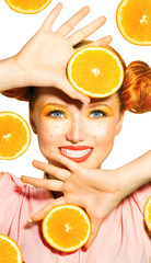 Beauty model girl takes juicy oranges. Freckles