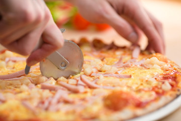 Pizza carbonara portions cutting by round knife